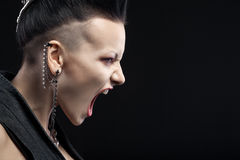 Verärgerte junge Frau, die auf schwarzem Hintergrund schreit Stockfoto