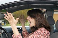 Verärgerte junge Frau, die in Auto fährt Stockfotos