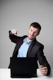 Verärgerter Geschäftsmann, der seinen Laptop schlägt Lizenzfreie Stockbilder