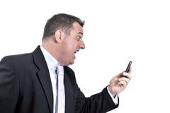 Verärgerter Geschäftsmann, der zu einem Handy schreit Stockbilder