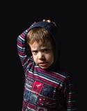 Verärgerter Junge mit dem Hoodie, der über schwarzem Hintergrund steht Lizenzfreie Stockfotografie