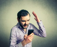 Verärgerter Mann, der am Telefon schreit Stockfoto