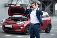 Verärgerter Mann, der telefonisch wegen des aufgegliederten Autos spricht Stockbild