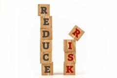 Verringern Sie das Risikowort, das auf Würfelform geschrieben wird stockbilder
