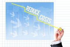 Verringern Sie Kostenkonzept mit Geschäftsmannhandabgehobenem betrag ein Diagramm Lizenzfreie Stockfotos