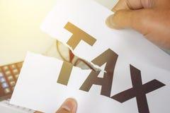 ` Verringern zerrissenes Papier Steuer ` Mannes Hände mit der Wortsteuer Geschäft Stockfoto