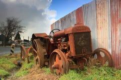 Verrostender Fordson-Traktor und Wellblechzaun stockfotografie