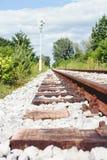 Verrostete Bahnstrecken und Lagerschwellen auf dem weißen Kies, umgeben mit dem Grün und blauem Himmel lizenzfreie stockfotos