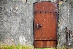 Verrostete Metalltür in der alten Wand, Hintergrundbeschaffenheit Lizenzfreies Stockbild