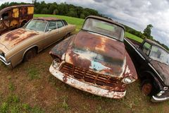 Verrosteter antiker Fahrzeug-Sit Lined Up In Auto-Autofriedhof Stockbild