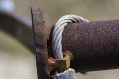 Verrostetes Metallteil des Zauns mit Seil Stockfoto