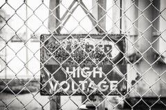Verrostetes Warnschild auf einem Kettenglied-Zaun Stockbild