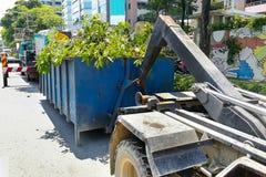 Verrou de récipient de déchets avec le camion plein des bois d'ordures de jardin images libres de droits