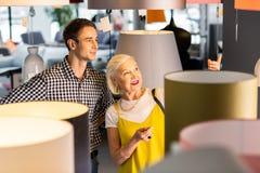 Verrukkelijk bejaard mevrouw die vriendaandacht besteden aan lamp die zij heeft gehouden van royalty-vrije stock foto