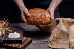 Vers artisanaal brood in de handen Het concept gezond voedsel en traditionele bakkerij royalty-vrije stock fotografie