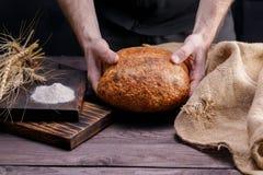 Vers artisanaal brood in mannelijke handen Het concept gezond voedsel en traditionele bakkerij royalty-vrije stock afbeelding