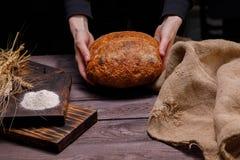 Vers artisanaal brood in vrouwelijke handen Het concept gezond voedsel en traditionele bakkerij royalty-vrije stock afbeelding