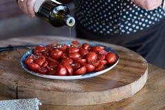 Vers Cherry Tomatoes onder olie en kruiden op de lijst, de zomerterras Royalty-vrije Stock Foto