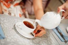 Vers? dans une tasse de th? photographie stock