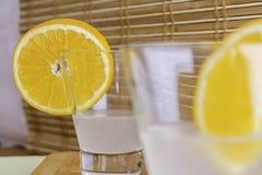 Vers die kokosnotenwater in glas met oranje plakken op houten dienblad en bamboe selectieve gestemde nadruk wordt verfraaid als a Royalty-vrije Stock Foto's