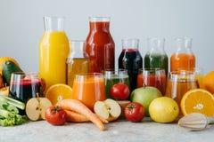 Vers die sap van diverse groenten en fruit in glaskruiken wordt gemaakt op grijze die lijst, over witte achtergrond wordt geïsole royalty-vrije stock afbeeldingen