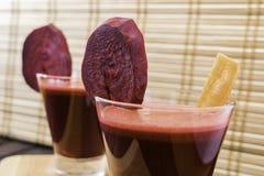 Vers die wortel en bietensap in glas met wortel en bietenplakken op houten dienblad en bamboe selectieve achtergrond wordt verfra Stock Afbeeldingen