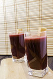 Vers die wortel en bietensap in glas met wortelplakken wordt verfraaid op houten dienblad en bamboe selectieve gestemde nadruk al Stock Foto