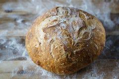 Vers eigengemaakt die brood van zuurdesem wordt gemaakt die op houten cuttnigraad rusten Artisanaal brood met gouden knapperige k stock afbeeldingen