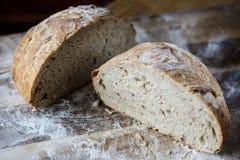 Vers eigengemaakt die brood van zuurdesem wordt gemaakt die op houten cuttnigraad rusten Artisanaal brood met gouden knapperige k stock fotografie