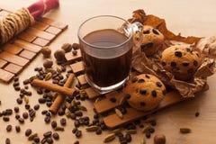 Vers, enkel gebakken die cupcakes met chocolade, kaneel en koffiezaden met kop van donkere koffie worden geplaatst Stock Afbeeldingen