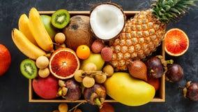 Vers exotisch fruit in een doos Gouden ananas, bloedsinaasappel, kokosnoot, mini longan bananen, stock foto's
