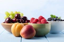 Vers Fruitkeuzen in Kommen op Lichtblauwe Houten Planked-Lijst Stock Foto's