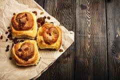 Vers gebakken broodjes met kaneel met kruiden en rozijnen op perkamentdocument Mening van hierboven Zoete eigengemaakte gebakjes  royalty-vrije stock fotografie