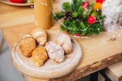 Vers gebakken croissants op een houten rondetafel tegen een houten lijst royalty-vrije stock afbeelding