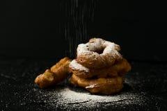 Vers gebakken donuts met de dalende donkere foto van het suikerpoeder Royalty-vrije Stock Afbeeldingen