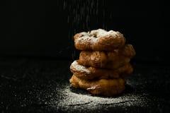 Vers gebakken donuts met de dalende donkere foto van het suikerpoeder Stock Foto's
