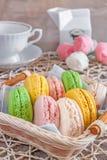 Vers gebakken macarons in een rieten mand met heemst en een Kop thee Stock Foto