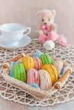 Vers gebakken macarons in een rieten mand met heemst en een Kop thee Royalty-vrije Stock Afbeeldingen