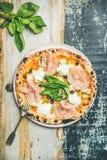 Vers gebakken pizza met ham, artisjokken, kaas, basilicum op plaat Royalty-vrije Stock Afbeeldingen