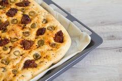 Vers gebakken traditioneel Italiaans focacciabrood met groene olijven en in de zon gedroogde tomaten Stock Afbeeldingen