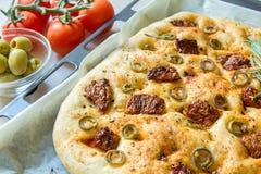 Vers gebakken traditioneel Italiaans focacciabrood met groene olijven en in de zon gedroogde tomaten Stock Afbeelding