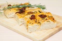 Vers gebakken traditioneel Italiaans focacciabrood met groene olijven en in de zon gedroogde tomaten Stock Fotografie