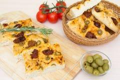 Vers gebakken traditioneel Italiaans focacciabrood met groene olijven en in de zon gedroogde tomaten Stock Foto's