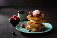 Vers gebakken wafels met frambozen, bessen, honing en koffie voor ontbijt of brunch op een donkere achtergrond met exemplaarruimt stock foto