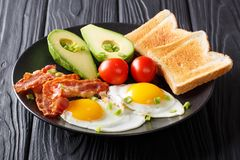 Vers gebraden eieren met knapperig bacon, avocado, toost en tomatoe stock afbeelding