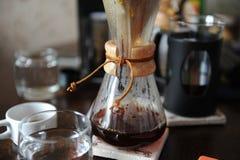 Vers gebrouwen koffie in een glaskruik op de achtergrond van koffietoebehoren stock fotografie