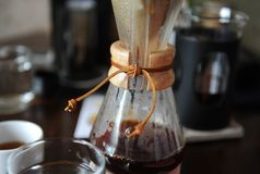 Vers gebrouwen koffie in een glaskruik op de achtergrond van koffietoebehoren stock foto