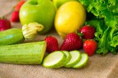 Vers gedetailleerd fruit - aardbeien, courgettes, citroen, appel en groene salade stock foto's