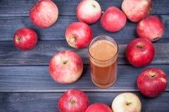 Vers gedrukt appelsapglas en rode appelen op de donkere houten mening van de lijstbovenkant Royalty-vrije Stock Foto's