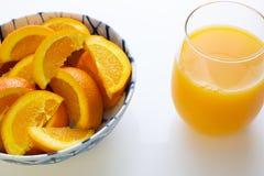 Vers gedrukt jus d'orange in een glas naast een kom van oranje plakken en twee die sinaasappelen enkel van de boom op een witte l royalty-vrije stock foto's